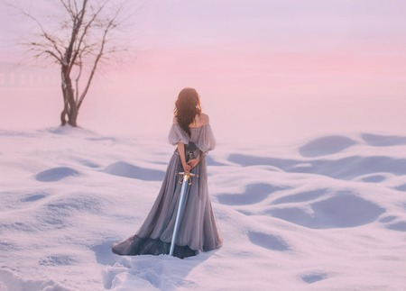 mysterious lady from Middle Ages with dark hair in gentle gray blue dress in snowy desert with open back and shoulders, sharp sword behind, model stands back with no face, creative pastel colors