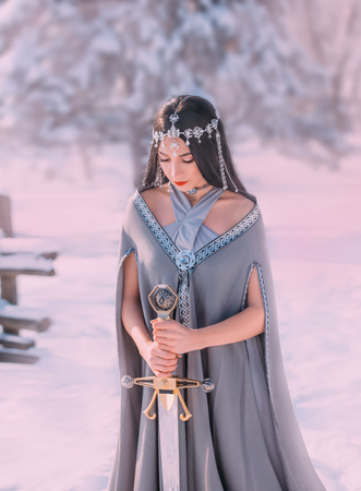 charming sweet dark-haired girl with closed eyes reads prayer to gods of war before terrible fight, elegant princess holds silver sword, meditation with weapon for hardening spirit of warrior Фото со стока