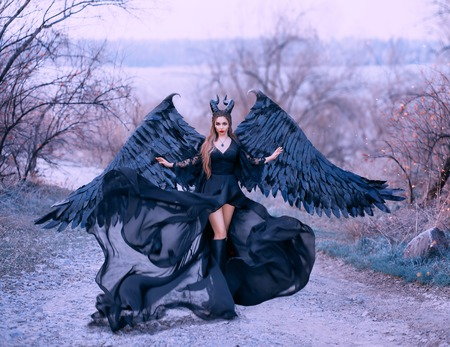 charming gorgeous dark witch controls wind, air flow waves hem and long train of light black dress with wide lace sleeves, lady with sharp horns and black feather wings ready to fly into sky Banco de Imagens