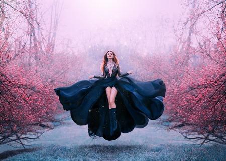 wunderschöne rothaarige heiße frau im langen fliegenden schwarzen kleid flattern, hexe verwandelt sich in krähe, dunkle königin im gefrorenen frühlingsblüherwald, levitation und flug, offen und beine. Standard-Bild