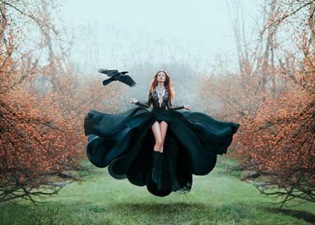 ragazza con i capelli rosso vivo levita dal suolo, potente maga, dea della foresta in abito nero volante con pizzo sul petto aperto e gambe lunghe, signora in un giardino fiorito di aranci e corvo a mano Archivio Fotografico