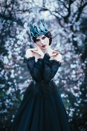grim lady with pale white skin and dark hair beside flowering tree, witch turns with black crow with long luxurious dress and open shoulders, gothic image and makeup, cold metal crown and jewels