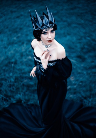 grim lady with pale white skin and dark hair beside frozen grass, witch turns with black crow with long luxurious dress and open shoulders, gothic image and makeup, cold metal crown and jewels