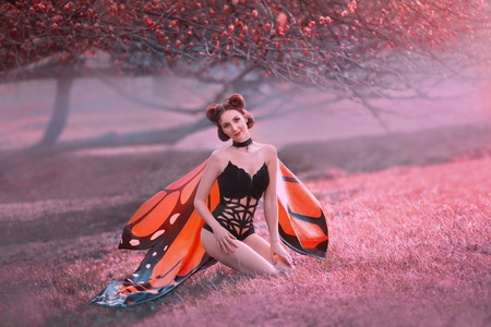 The girl is a monarch butterfly, sits on the grass and coquettishly looks into the camera. Forest red-haired fairy with a creative hair style in pin-up style. Sexy, slim goddess with a perfect body.