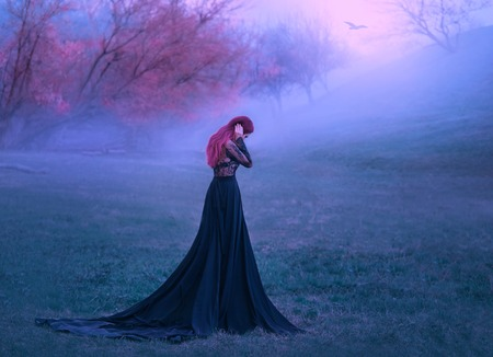 A sad lady in a black dress unhappy wanders in the fog. Background of autumn trees and hills. A lonely bird flies. A woman hugs her head in grief and cries. Pink hair. Art photo from the back, no face