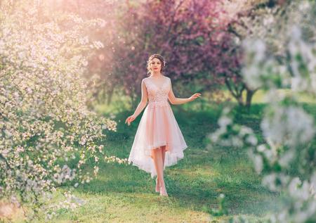 geheimnisvolle Dame mit dunkel gerafftem Haar in einem leichten zarten Pfirsichkleid geht durch den blühenden Garten, die Frühlingsfee berührt ihr Hab und Gut, die Märchenelfe wie eine Puppe auf dem Gras barfuß Standard-Bild