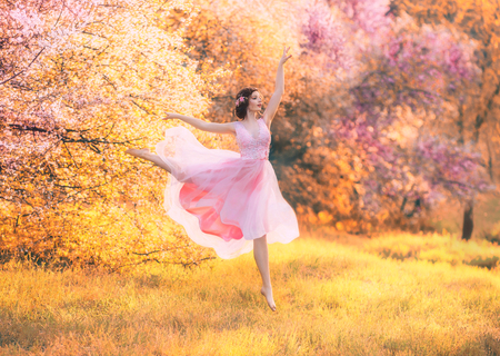 revived porcelain doll in flying pink dress dancing in flowering spring forest, tender lady with dark hair in bright yellow garden, fabulous ballerina enjoys warm days, fairy flight, creative colors