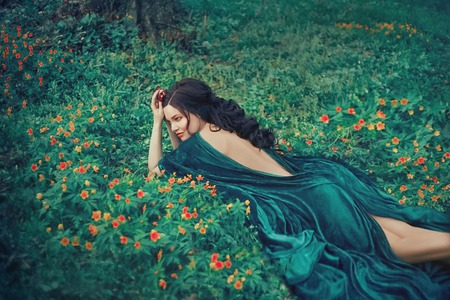 charming nymph lying on green grass and bright small flowers, girl in a long emerald velor dress with open bare back is resting in a clearing, forest fairy with dark hair observes life of forest