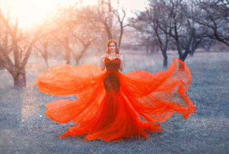 queen in bright long elegant flying red dress poses for photo, woman with dark hair and crown on her head puts hands on her shoulders, sorceress objects to life of forest in sun rays, creative colors Imagens