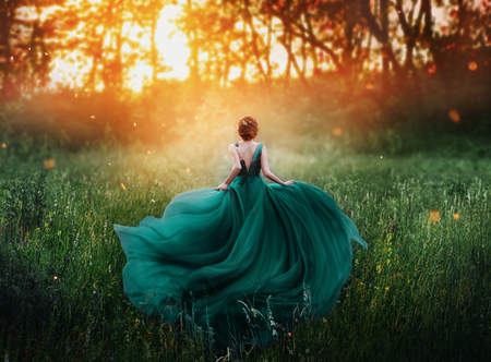 magical picture, girl with red hair runs into dark mysterious forest, lady in long elegant royal expensive emerald green turquoise dress with flying train, amazing transformation during fiery sunset. Stockfoto