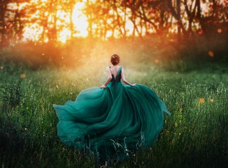 magiczny obrazek, rudowłosa dziewczyna biegnie do ciemnego tajemniczego lasu, dama w długiej eleganckiej królewskiej drogiej szmaragdowozielonej turkusowej sukience z latającym pociągiem, niesamowita przemiana podczas ognistego zachodu słońca.
