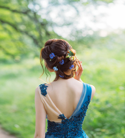 unusual cool chic hairstyle for long dark hair, work of hairdresser, image for graduation and wedding, forest nymph with flowers in a hairstyle, gentle image, an art photo from back without a face.