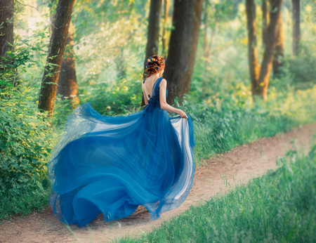 mysterious girl with red braided hair runs off from royal holiday, lady in long elegant blue dress with flying light train like flower, the magical transformation of beautiful woman during sunset.