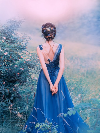art processing of creative photos with unusual cool flowers, a sweet girl with black flown hair, decorated flowers, a lady in a long blue elegant dress with a bold cut on the back, forest princess. Banco de Imagens - 124955194