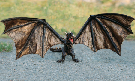 powerful strong dragon with black thick scales, a mythical fairy-tale creature opened his mouth for collage, frightening power of an animal with large and sharp fangs and claws, wide wings