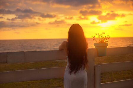 dark-haired girl with chic figure put her hands on a fence with a flower pot, a lady in white dress, looks at bright red and yellow sunset in sea with a cloudy sky. photo without face from back Banco de Imagens