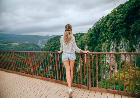 mysterious lady goes to bridge, lady with blond hair and long legs, tourist in casual clothes, bright colors and gorgeous beauty of mountains and forests. photo from the back no face Banco de Imagens - 124871321