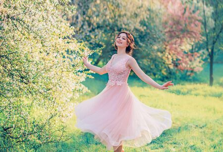happy girl in short flying gentle pink dress laughs joyfully, doll princess whirls in bright yellow spring garden with flowering trees, positive emotions, movement in photo with creative colors Stockfoto