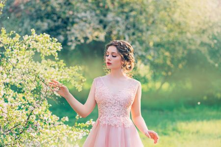 charming lady in blooming garden, girl with gathered hair gently strokes branches of trees with flowers, porcelain doll with bright red cute lips in pink dress, image of spring nymph, creative colors Stockfoto