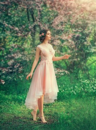 pretty slender girl with braided dark hair with a barrette in a delicate elegant peach dress, a fairy-tale princess in a frozen flowering forest, a gentle image of the queen, fairy in love