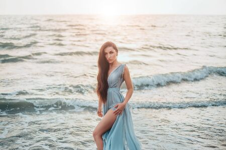 queen of sea emerged from ocean and threateningly looks at world of dry land, long haired brunette beauty poses in long gentle blue dress and shows bare long leg, mysterious mermaid, wave daughter Standard-Bild - 124871374
