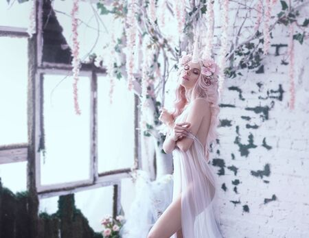 Wonderful creation, the girl is a unicorn in light, white, slightly transparent attire. The background is a bright room that is overgrown with plants, moss, ivy, trees and flowers. Art Photo.