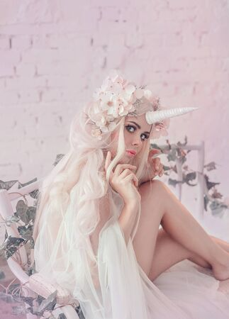 Wonderful creation, the girl is a unicorn in light, white, slightly transparent attire. The background is a bright room that is overgrown with plants, moss, ivy, trees and flowers. Artistic Photo.