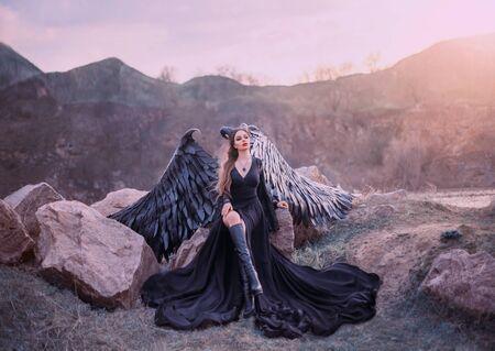 gárgola revivida, reina de la noche viendo el amanecer, niña con vestido largo negro claro con alas de plumas negras sentada sobre rocas con la pierna abierta en botas altas, misteriosa criatura mítica, foto de arte creativo Foto de archivo
