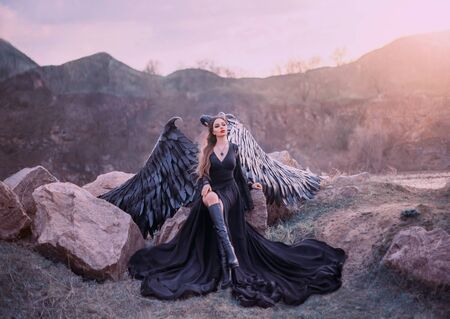 revived gargoyle, queen of night watching sunrise, girl in long light black dress with black feather wings sits on rocks with open leg in high boots, mysterious mythical creature, creative art photo Stockfoto