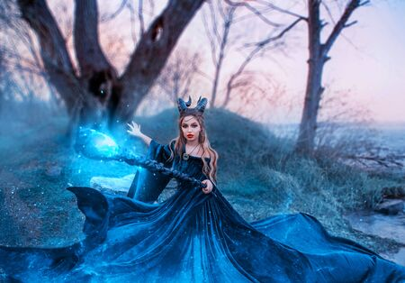 strict witch with magical magical glowing and sparkling staff in her hands, lady with horns on head utters spell, emerald silk flying long dress, demonessa on grassy bank of river during sunset Standard-Bild - 124871392