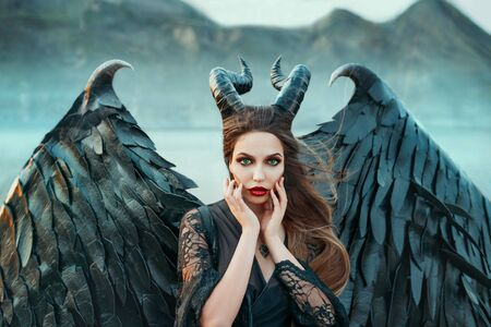 charming portrait of dark angel with sharp horns and claws on strong powerful wings, wicked witch in black lace dress brought hands to face, bright red lipstick and green eyes, art photo in blue shade Stock Photo