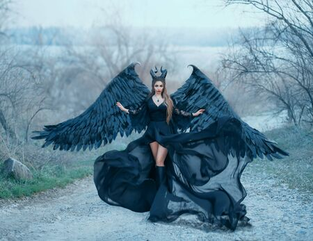 encantadora hermosa diosa oscura controla el viento, el flujo de aire, el dobladillo de las ondas y la larga cola de un vestido negro claro con mangas anchas de encaje, una dama con cuernos afilados y alas de plumas negras lista para volar hacia el cielo