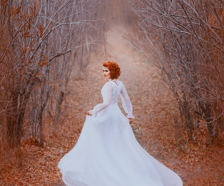 The redhead princess in a white vintage dress runs in a tunnel from the trees and looks back. Luxurious outfit with a long train flutters in the wind. Sleeping nature, golden autumn, warm colors