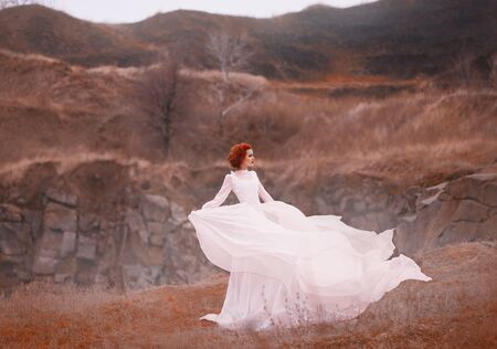 Red-haired beauty in a white vintage dress, stands on top of a hill, Background of the rocky mountains. Luxurious outfit with a long train flutters in the wind. Light flying silk fabrics. warm colors Standard-Bild - 124871399
