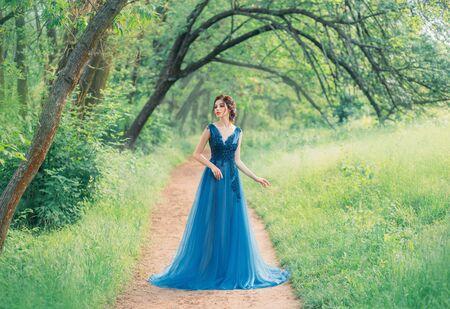 un'incredibile principessa del mare che cammina da sola attraverso una foresta fatata rossa, una fata magica con un vestito verde turchese, una graziosa ninfa dai capelli scuri come un fiore magico, una signora su un sentiero segreto, colori creativi Archivio Fotografico