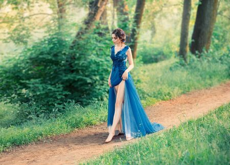 The girl in the evening, luxurious, watercolor dress, with a high slit. long legs. The image of the party, a young charming graduate. Collected hairstyle with weaves, hair decorated with blue flowers