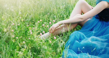 charming delicate art photo with creative colors, the lady touches the fingers of the hand of her sexy bare legs, the princess in a long blue lush chic elegant dress, free space for text, no face