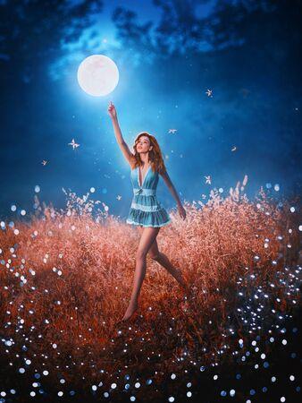 hübsche langbeinige Schönheit mit fliegenden, fließenden Haaren läuft durch das Feld gefallener Sterne hinter dem mystischen schwebenden Mond. Erstaunliches Kunstfoto mit kreativen Farben. Mädchen im Bild der Nachtfee im kurzen blauen Kleid