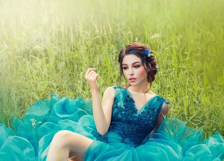 charming mysterious story about porcelain doll, lovely girl in long blue lush delicate dress. lady with dark braided hair and gentle make-up, perfect skin, flower in green grass on fresh nature