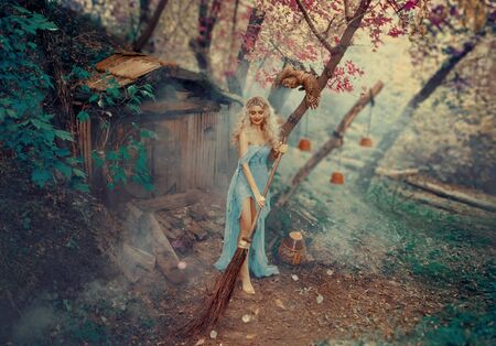 The good sorceress, the Cinderellas fairy godmother, dances and sings while cleaning up the courtyard of her little house hidden in the forest. A simple, battered, old gray dress. curly, blond hair Фото со стока