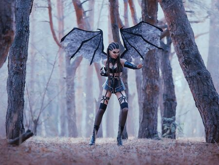 wild bat protects forest from strangers, passionate demoness in latex leather short skirt and stockings with dark makeup and creative hair, aggressive satan woman with long claws and wings