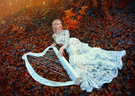 excellent princess with blond hair in long lace vintage dress lies on red dark leaves, girl resting in autumn forest, fairy-tale queen with magical harp sings forest songs in bright rays of sun