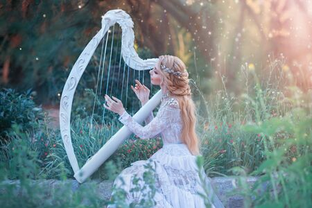 mysterious forest nymph plays on white harp in fabulous place, girl with long blond hair and elegant lace vintage dress calling for bright sun rays, lady with silver jewelry and musical instrument