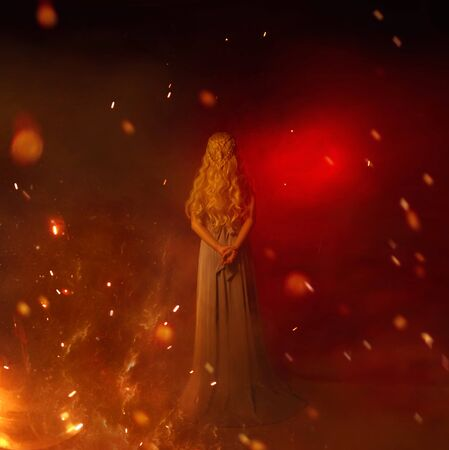 mistress of fire in red room full of flame and burning sparks, lady with long curled white blond hair in gray vintage dress, girl with hands behind her back, young woman with highlights and heat 版權商用圖片