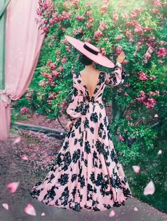 lady in long pink dress with black patterns. Woman in the last thing in hats with wide brimmed touches roses with back to camera, no face. Falling, flying rose petals, like hearts. Valentines Day