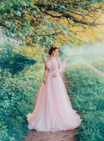 tender innocent girl confusedly looks away, forest fairy walks over her possession, attractive young bride with dark hair in long pink dress to floor, creative colors, blue green grass and trees
