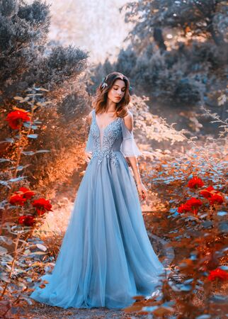 sad princess walks in fading autumn garden with withered plants, lady with short dark hair in chic light blue sky dress looks at red roses with sadness, clean young attractive girl, creative colors