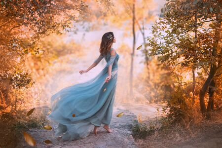 delightful light girl in sky blue turquoise dress with long flying train, princess of wind and daughter of storm, lady with dark hair throws fallen leaves to ground, autumn story in art processing Standard-Bild