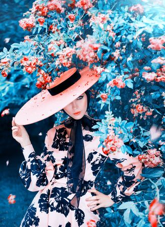 charming girl hides part of her face under wide-brimmed pink hat with ribbons. Lady with warm orange make-up in garden of blooming roses under hood of summer rain, Girl flirts on happy valentines day 免版税图像