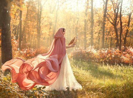 brillante foto de verano de misteriosa belleza en el bosque matutino, dama con vestido blanco brillante y capa rosa melocotón con cola larga y capucha, de espaldas a la cámara y cara vuelta, niña con cabello oscuro y lechuza común